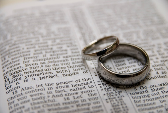 two wedding rings on a page of the Bible